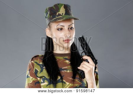 Female soldier in camouflage uniform with weapon isolated on gray background