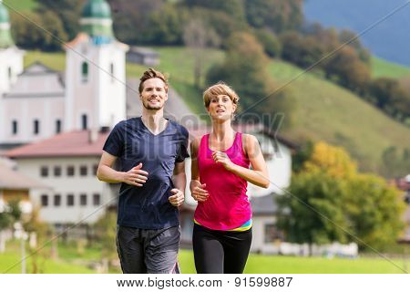 Couple doing sport running in the mountains