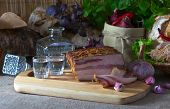 picture of vodka  - Vodka and smoked meat with garlic on kichen table  - JPG