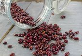 foto of kidney beans  - dried red kidney beans tumbling out of a glass jar - JPG
