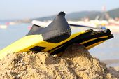 image of flipper  - yellow and black colored flipper over the sands - JPG