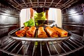 stock photo of oven  - Housewife preparing cakes in the oven at home - JPG