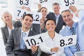 stock photo of interview  - Smiling interview panel holding score cards in bright office - JPG