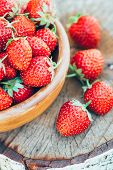 foto of strawberry  - Strawberries. Organic Berries Closeup. Ripe Strawberry In The Fruit Garden, Old Wooden Bowl Filled With Succulent Juicy Fresh Ripe Red Strawberries On Old Birch Stump ** Note: Shallow depth of field - JPG