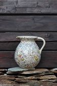 stock photo of jug  - The antique jug with a pattern of flowers lies on brown wood under a stone - JPG