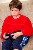 image of video game controller  - young boy playing a video game sitting on a couch - JPG