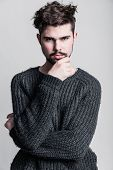 stock photo of pullovers  - Portrait of a young man in gray pullover - JPG