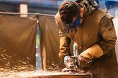 image of protective eyewear  - Young man with protective goggles welding in a factory - JPG