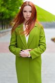 picture of ombres  - beautiful sexy woman  with fiery red hair with green coat walking through the streets of the city - JPG