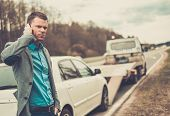picture of pick up  - Man calling while tow truck picking up his broken car  - JPG
