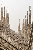 foto of stone sculpture  - Detail vertical view of stone sculptures on roofs of Duomo Milano Italy - JPG