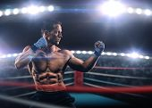 foto of boxing  - A strong man in the ring in blue boxing bandages preparing for battle - JPG