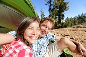 foto of two women taking cell phone  - Selfie camping couple in tent taking self portrait using camera smartphone - JPG