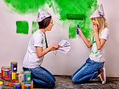 stock photo of newspaper  - Happy woman in homamade newspaper hat paint wall at home - JPG