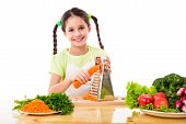 pic of grated radish  - Smiling girl grate the carrots on the table with vegetables - JPG