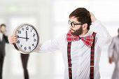 image of suspenders  - Worried man wearing suspenders holding big clock - JPG