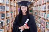 picture of graduation  - Portrait of female graduate student standing in the library while wearing graduation gown and holds a diploma - JPG