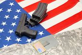 picture of handgun  - Handgun and US army uniform over US flag - JPG