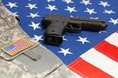 picture of handgun  - Handgun and US army uniform over huge US flag - JPG