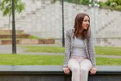 image of sitting a bench  - Beautiful young trendy woman wearing gray jacket and pink jeans sitting on a park bench  - JPG