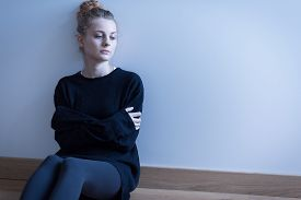 stock photo of anorexic  - Young woman with anxiety disorder sitting on the floor - JPG