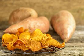 stock photo of potato-field  - Freah homemade sweet potato chips on a rustic background.