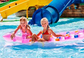 image of inflatable slide  - Kids are floating on inflatable mattress in water park - JPG