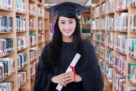 picture of graduation gown  - Portrait of female graduate student standing in the library while wearing graduation gown and holds a diploma - JPG