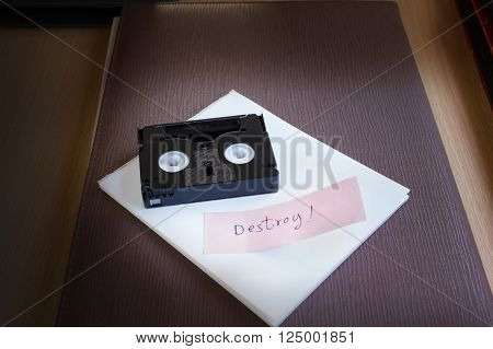 Mini Dv Cassette Tape On Note Text Word Destroy In Dim Light Room Nackground With Copy Space
