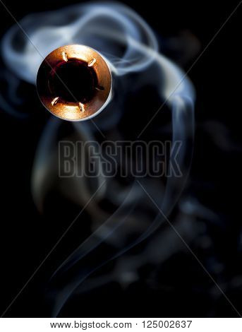 Copper color bullet and smoke on a black background