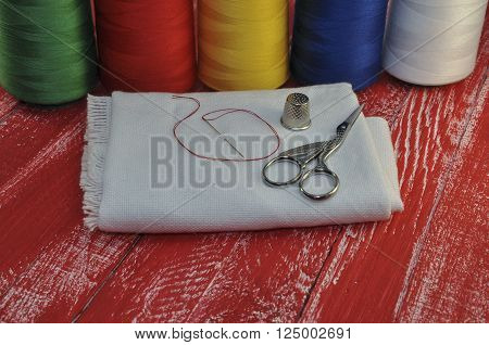 Colored thread fabric scissors a thimble for home crafts on the background of old red wooden table