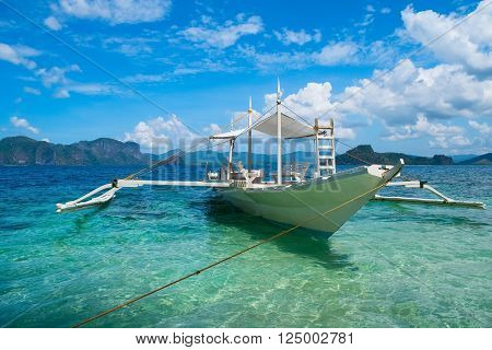 Traditional wooden boat in clear sea water, El Nido, Palawan, Philippines