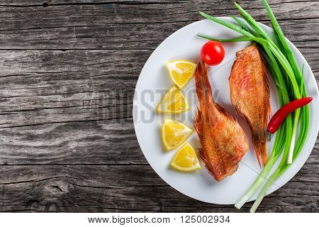 Red Sea Bass on a white dish with green spring onions lemon slices and cherry tomato on an old wooden table horizontal top view