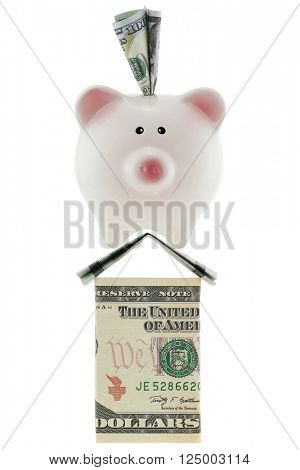 American 100 dollar currency in pink piggy bank standing on house made of U.S. money isolated on white ideally representing home savings, loans, real estate industry.