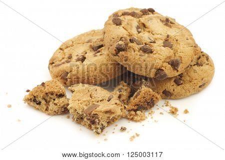 crunchy chocolate chip cookies and some pieces and crumbs on a white background