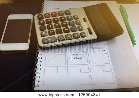 Organizer Book And Text Tax Payment In Dim Light Room With Blurred Calculator And Cellphone On Table