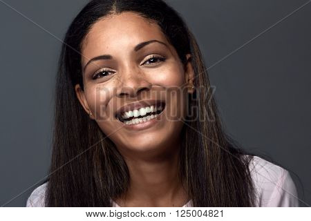 Natural smiling portrait of a hispanic latino indian asian woman against dark grey background