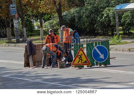 Kiev Ukraine - September 10 2015: Utility workers in orange vests repair asphalt on the road