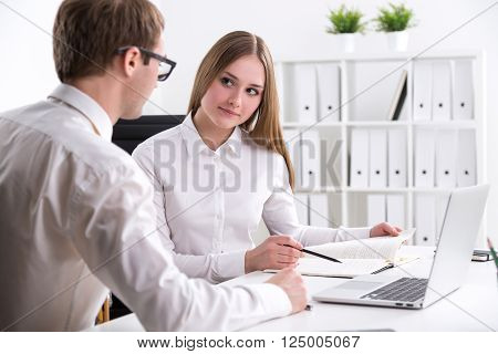 Businessman sitting next to businesswoman who is looking through notes office at background. Concept of explanation.