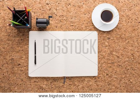 Brown cork table with blank open copybook, coffee cup and other items. Mock up