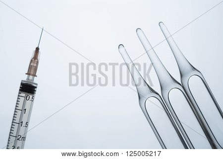 Three ampoules and syringe isolated on light background