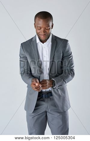 Candid portrait of african business man in grey suit adjusting his suit jacket