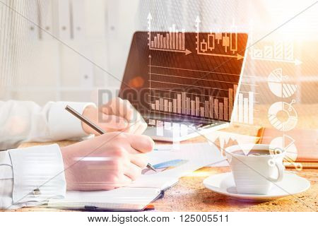 Sideview of desktop with businessman drawing graphs in copybook. Double exposure