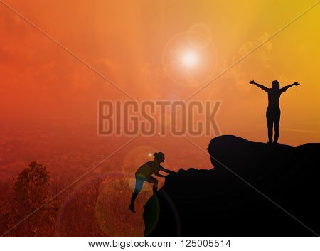 Women Silhouette Climbing And Standing On Cliff With Blurred City Topview And Sunlight