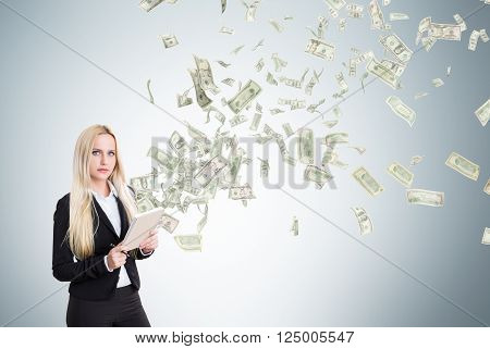 Young businesswoman with notebook dollars flying from it. Grey background. Concept of making money.
