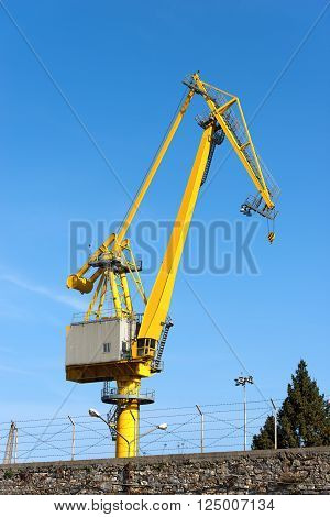 Large yellow and orange crane in the harbor of La Spezia Liguria Italy