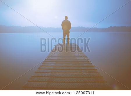 Man standing on a jetty by tranquil lake.