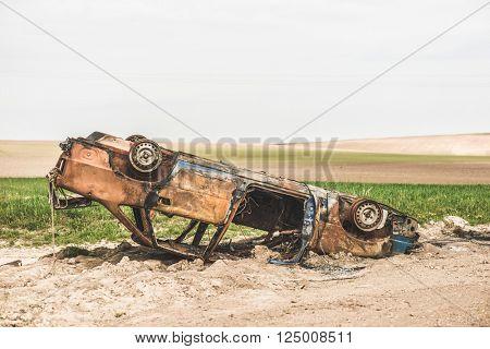 Abandoned rusty burnt car wreck.