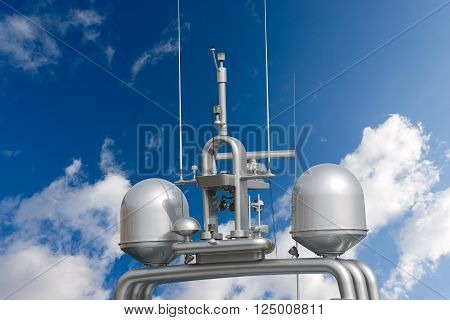 Detail of luxury grey yacht with navigation equipment, radar and antennas on blue sky with clouds