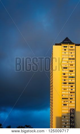 Waikiki, Honolulu, Hawaii, USA - December 14, 2015: Building lit by the warm afternoon sun and the background approaching storm cloud.